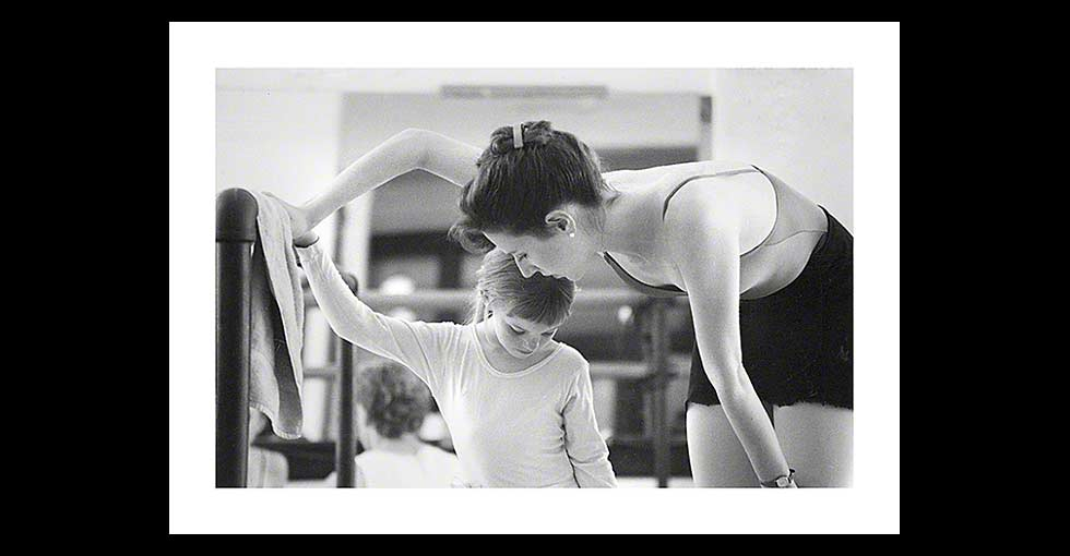 Ballerina with young ballet student at the barre in rehersal studio