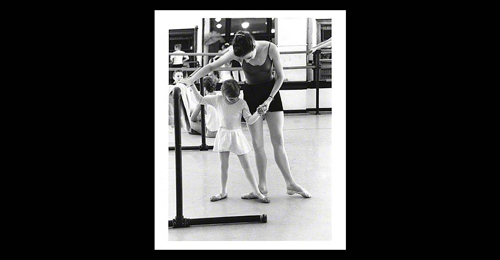Ballerina with young female ballet student at the bar