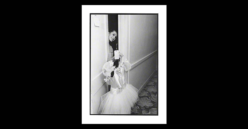 Ballerina holding tutu while opeing dressing room door