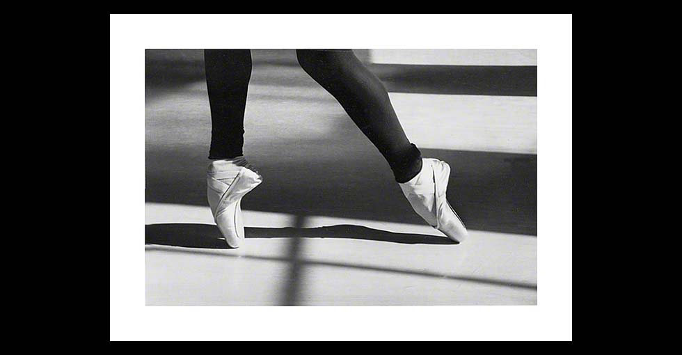 Close up of ballet dancer's feet with long shadows of light