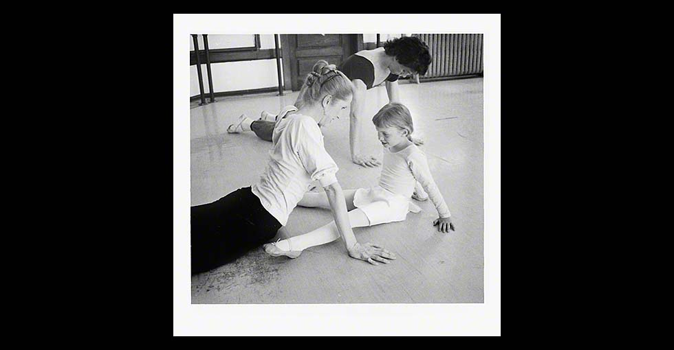 Ballerina with young ballet student sitting on floor in rehersal studio